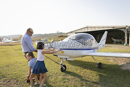 children and grandfather pulling airplane outside