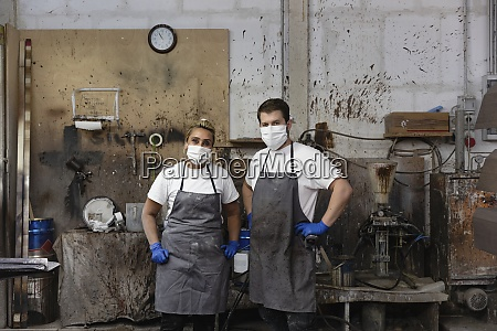confident carpenters standing with hand on