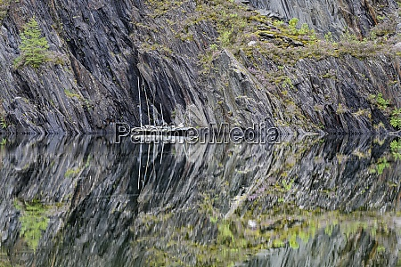 slate cliffs reflecting in clear shiny
