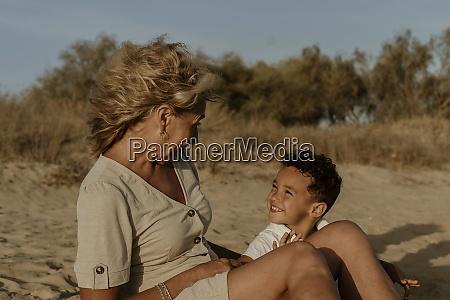 grandmother and grandson sitting on sand