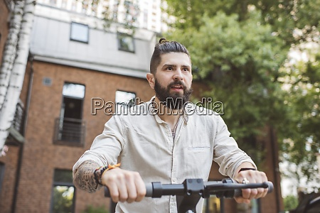 hipster man riding electric push scooter