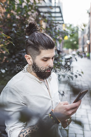hipster man using smartphone while standing