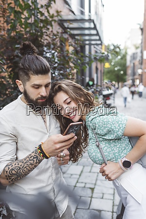 hipster man showing smart phone to