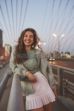smiling woman standing on bridge against