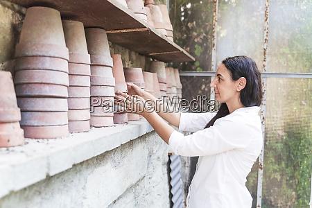 mature woman arranging pot while standing