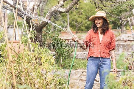 smiling beautiful mature woman watering plants