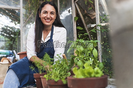 smiling woman sitting in garden shed