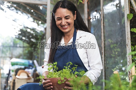 mature woman holding plant while sitting
