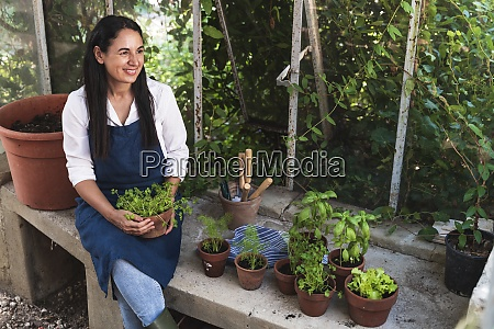 smiling mature woman holding plant looking