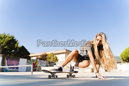 confident young blond woman skateboarding at