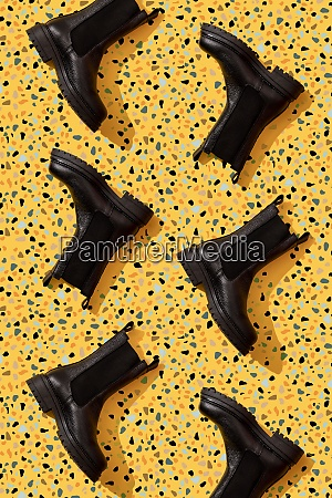 black leather boots on yellow terrazzo