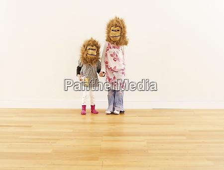 two girls wearing monkey masks standing