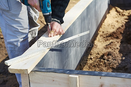 gardener screwing on wooden plank to