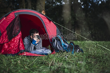 man camping in estonia lying in