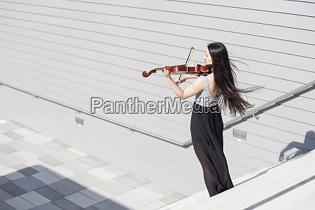young female asian playing violin on