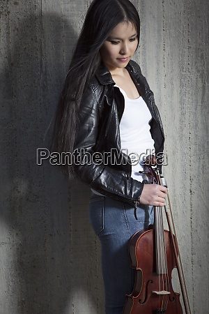 young female asian violinist leaning at