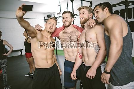 four athletes in gym taking selfie