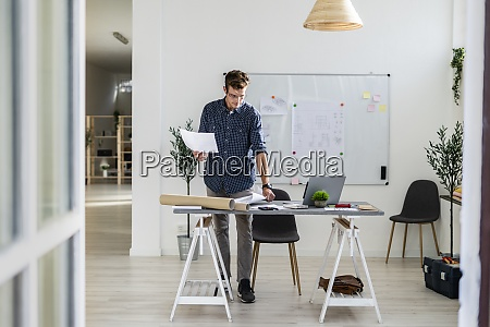 young man standing while working at