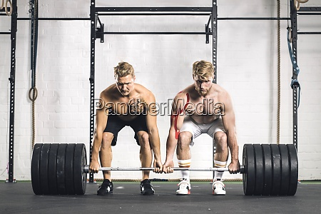 two young men in gym lifting