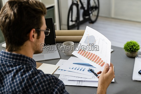 architect analyzing graph while sitting by