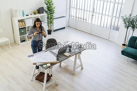 female architect photographing blueprint at desk