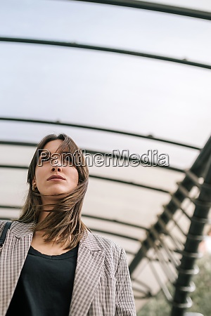 young woman standing under covered roof