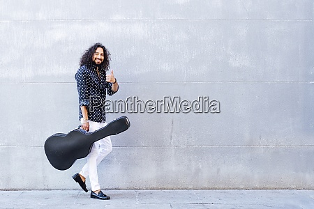 smiling man with guitar showing thumps