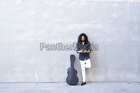 man with guitar using mobile phone