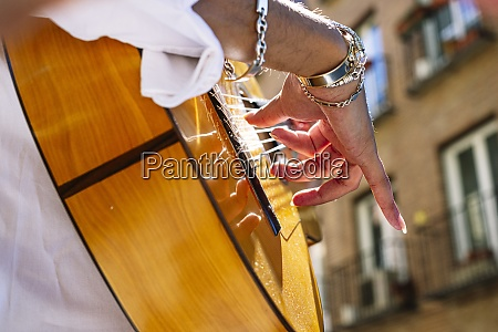 man plucking guitar string while standing