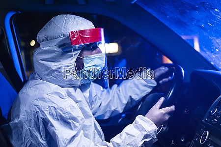 man wearing protective suit driving ambulance