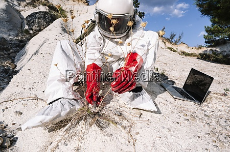 male astronaut picking plant while sitting