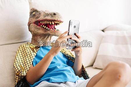boy wearing dinosaur mask and cape