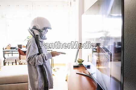 boy wearing space helmet watching tv