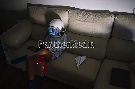 boy wearing space helmet sitting with