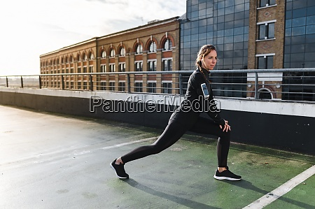 female athlete stretching legs on rooftop