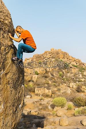 male rock climber ascending rock wall