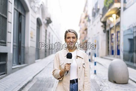 female journalist talking over microphone while
