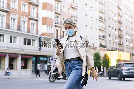young woman wearing mask using mobile