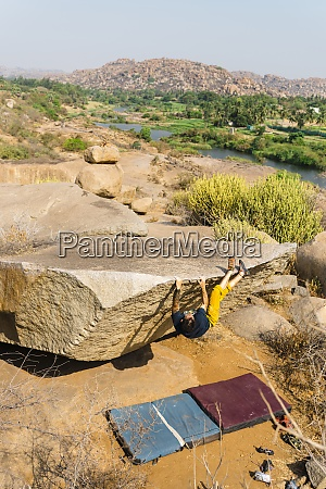 male rock climber getting on top