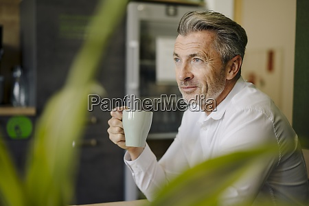 man drinking coffee while sitting by