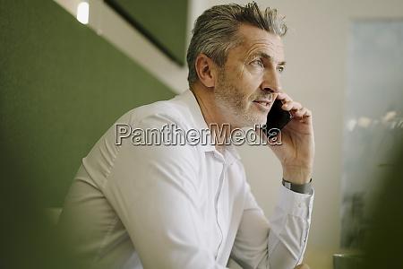man talking on phone while sitting