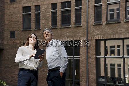 businessman and woman looking up while