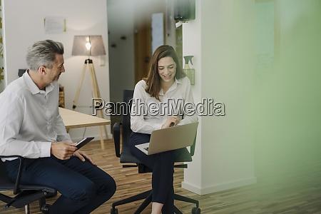 smiling woman using laptop while sitting