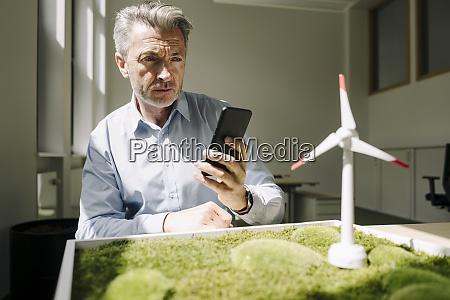 businessman taking photo of wind turbine