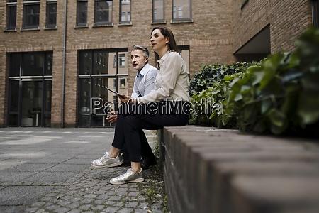businesswoman and man sitting on retaining