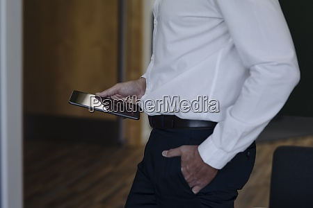 businessman with hands in pockets holding