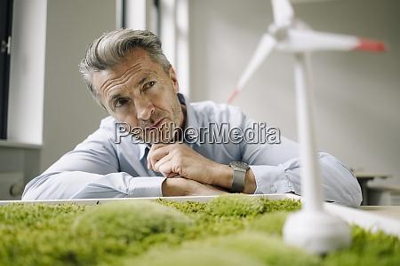 businessman looking at wind turbine toy