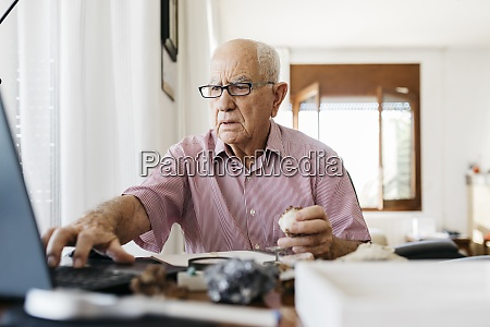 retired elderly man using laptop while