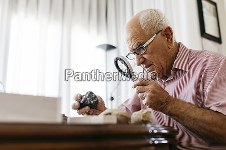 retired senior male using magnifying glass