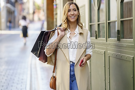 woman carrying shopping bag while standing
